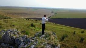 Il violinista gioca il violino su un plateau roccioso stock footage
