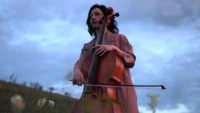 Il violoncellista della donna gioca il violoncello sul prato al crepuscolo archivi video