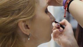 Il visagiste professionale fa il trucco per la donna matura nel negozio di bellezza stock footage