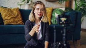 Il vlogger attraente della giovane donna sta registrando il video circa le spazzole ed i cosmetici La ragazza sta tenendo la spaz stock footage
