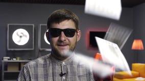 Il vlogger sveglio dell'uomo parla e tiene la pistola di plastica che sputa fuori le banconote del dollaro video d archivio