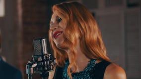 Il vocalist con le labbra rosse esegue in scena al microfono di concerto con il sassofonista archivi video