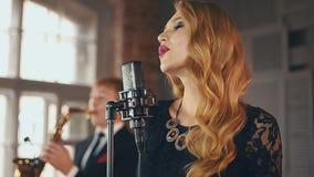 Il vocalist grazioso in vestito rosso con luminoso compone per eseguire in scena saxophonist stock footage