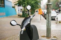 Il volante di un motorino elettrico è nella priorità alta, nei precedenti è una vista urbana della via di Berlino Immagine Stock