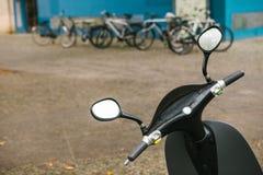 Il volante di un motorino elettrico è nella priorità alta, nei precedenti è una vista urbana della via di Berlino Fotografia Stock