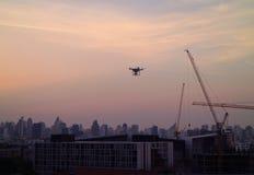 Il volo del fuco nel cielo porpora pastello di sera sopra la costruzione cranes Immagine Stock