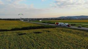 Il volo del paracadute di Moto lungo la strada sopra i girasoli sistema sul tramonto video d archivio