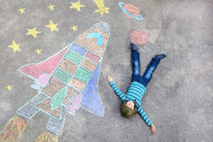 Il volo del ragazzo del bambino da una navetta spaziale segna l'immagine col gesso Immagine Stock