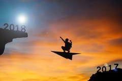 Il volo del ragazzo della siluetta con il razzo va alla parola 2018 Fotografia Stock