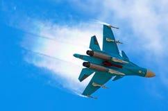 Il volo dell'aereo da caccia di battaglia si tuffa rompendo le nuvole su un cielo blu Fotografia Stock