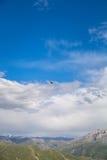 Il volo dell'uccello su un cielo blu con si rannuvola i picchi di montagna nel Kirghizistan Fotografie Stock Libere da Diritti