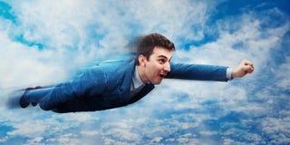 Il volo dell'uomo d'affari gradisce un supereroe Fotografia Stock