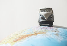 Il VW d'annata trasporta sul globo Immagine Stock