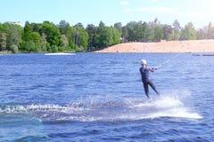 Il wakeboarder dell'atleta esegue un salto con un salto mortale nell'aria fotografie stock