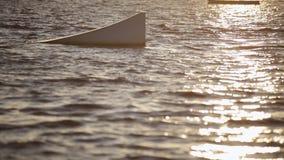 Il wakeboarder maschio fa scorrere uniformemente alla velocità sul fiume fra i trampolini dell'acqua video d archivio