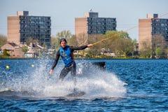 Il Wakeboarder sta facendo il suo trucco alla pista di Wakeboard fotografia stock libera da diritti