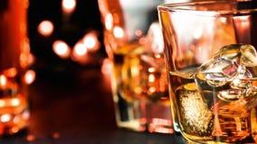 Il whiskey di versamento sulla barra presenta vicino all'atmosfera calda delle bottiglie archivi video