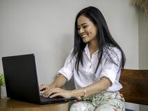 Il worikng asiatico attraente della donna di affari con lo schermo del labtop concentra il suo lavoro come crea il contenuto di p fotografie stock