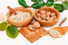 Il y a avec des noix et l'avoine roulée dans les plats en bois avec des bâtons de Sinnamon, appui en bois, cuillère, vert part, F Photographie stock libre de droits