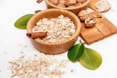 Il y a avec des noix et l'avoine roulée dans les plats en bois avec des bâtons de Sinnamon, appui en bois, cuillère, vert part, F Photo libre de droits