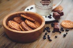 Il y a des biscuits, sucrerie, pois de chocolat, pavot ; Soucoupe en porcelaine et chapeau avec Coffe, nourriture douce savoureus Images libres de droits