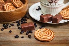 Il y a des biscuits, sucrerie, pois de chocolat, pavot ; Soucoupe en porcelaine et chapeau avec Coffe, nourriture douce savoureus Image stock