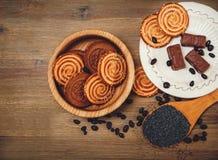 Il y a des biscuits, sucrerie, pois de chocolat, pavot ; Soucoupe en porcelaine, nourriture douce savoureuse sur le fond en bois, Images stock