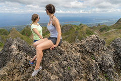 il y a deux jeunes femmes aux montagnes sous le ciel nuageux avec le fond de paysage marin Photos libres de droits
