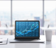 Il y a un ordinateur portable avec le diagramme de forex sur l'écran, tampon et une tasse de café sur la table Un lieu de travail Photo stock