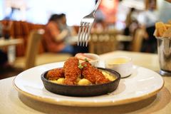 Il y a une fourchette au-dessus du poulet sans os frit croquant et du fromage fondu contenus dans la casserole en acier chaude se Image stock