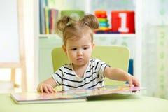 Ila lite flickan som ser boken, medan sitta på stol i barnkammare Royaltyfri Bild