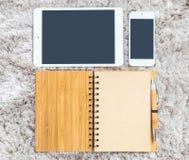 Ilar den bruna anmärkningsboken för closeupen med tomt utrymme i sidan, den bruna pennan, minnestavla och telefonen på grå textur Royaltyfri Bild