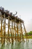 Ildren sautant du long pont en bois de lundi endommagé Image stock