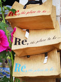 Ile de Re. (Island of Re): Shopping bags in a souvenir shop with a Hollyhock flower on foreground (typical of the island)  in France, Atlantic ocean Stock Photos