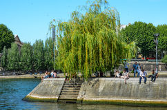 Ile St. Louis in Paris. People rest on the banks of Ile St. Louis, one of two islands in the middle of the Seine River Stock Photo