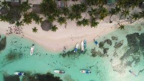 Ilha das Cara?bas tropical Saona, Rep?blica Dominicana Praia, palmeiras e barcos de navigação selvagens, opinião aérea do zangão vídeos de arquivo