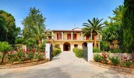 ILHA DE CORFU, GRÉCIA, JUNHO, 03, 2014: A entrada grega agradável da porta do hotel entre rosas das palmas floresce árvores verde Foto de Stock Royalty Free