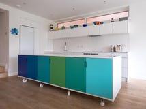 Ilha de cozinha projetada na cozinha de plano aberto nas rodas industriais do rodízio, no projeto retro pintados em cores azuis e imagem de stock