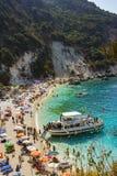 Ilha de Lefkada, praia de Agiofilli, Grécia Férias de verão, muitos povos na praia, natação do mar imagem de stock
