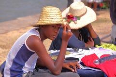ILHA DE RODRIGUES, MAURÍCIAS - 10 DE NOVEMBRO DE 2012: Um menino local novo com um chapéu de palha no mercado no porto Mathurin Fotografia de Stock