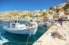 ILHA DE SYMI, GRÉCIA, O 25 DE JUNHO DE 2013: A vista em barcos de mar piscatórios velhos clássicos bonitos envia, o porto marítim Imagens de Stock Royalty Free