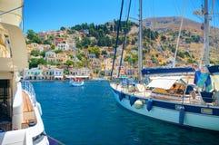 ILHA DE SYMI, GRÉCIA, O 25 DE JUNHO DE 2013: A vista no oceano clássico bonito do mar yachts, o porto marítimo grego, casas em mo imagem de stock royalty free