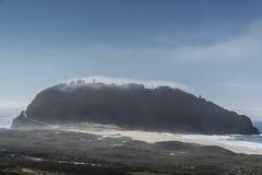 Ilha nevoenta misteriosa com construções e Misty Clouds Imagem de Stock Royalty Free