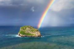A ilha nomeou Aketxe em Bermeo com nuvens tormentosos e um arco-íris Imagens de Stock Royalty Free