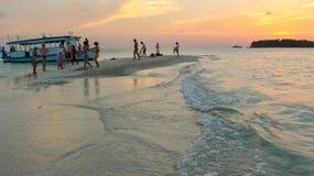 Ilha pequena com os povos de relaxamento no mar de Maldivas no por do sol Imagens de Stock