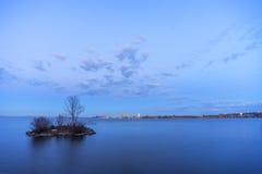 Ilha pequena no lago liso no crepúsculo que esconde uma cisne do assentamento, safel imagem de stock royalty free