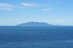 Ilha vulcânica cercada pelo mar foto de stock