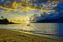 Ilhabela beach Pereque with boat in the sea at sunset - Sao Paulo, Brazil - wide angle photo. Photo of Ilhabela beach Pereque with boat in the sea at sunset royalty free stock image