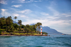 Ilhabela coast lighthouse. Coast of Ilhabela with clear blue water and a lighthouse Royalty Free Stock Photography
