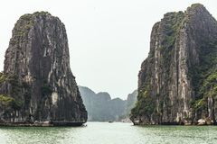 Ilhas da pedra calcária no lado esquerdo e direito sobre a água esmeralda com o céu brilhante no verão em Quang Ninh, Vietname foto de stock